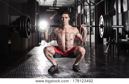 Attractive muscular bodybuilder doing  squat exercise in modern fitness center.
