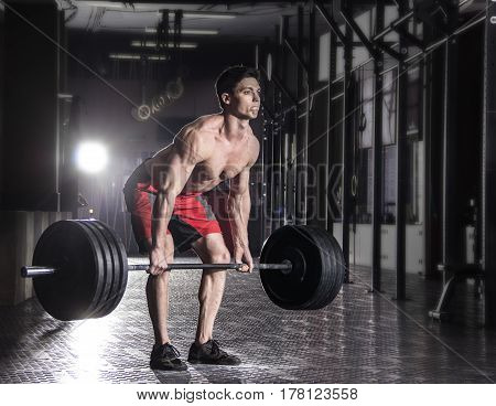 Attractive muscular bodybuilder doing heavy deadlift exercise in modern fitness center.