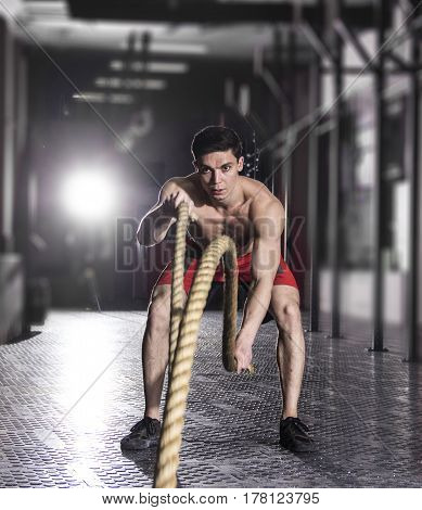 Muscular man with battle rope battle ropes exercise in the fitness gym. CrossFit.