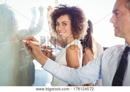 Businesspeople writing on white board in office
