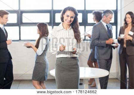 Successful businesswoman smiling at camera while her colleagues standing behind her in office