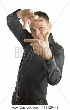 Focus on executive making frame with his hands on white background. Young happy man making frame with his hands looking at camera and smiling standing against isolated white background. He is dressed in a black shirt