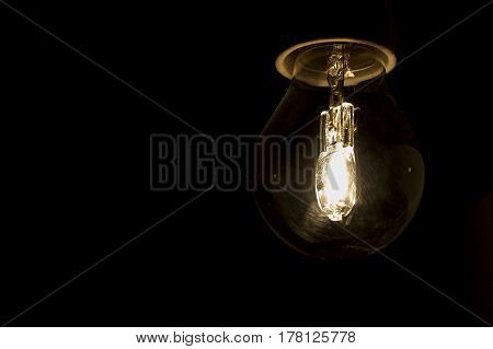 Close Up Glowing Vintage Light Bulb. Isolated On Black Background