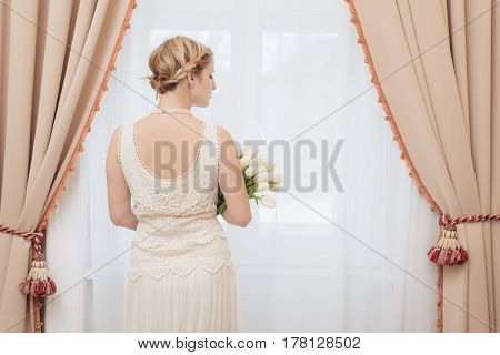 Bride in hotel room standing by the window