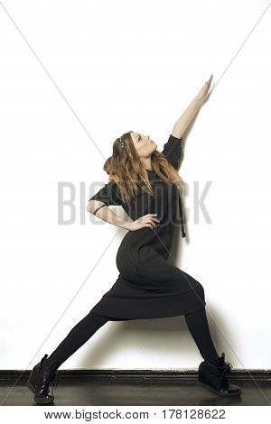 Model girl of unearthly beauty, perfect body and face, on a white background in a black suit