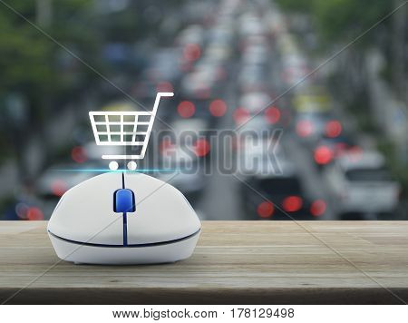 Shopping basket icon with wireless computer mouse on wooden table over blur of rush hour with cars and road Shop online concept
