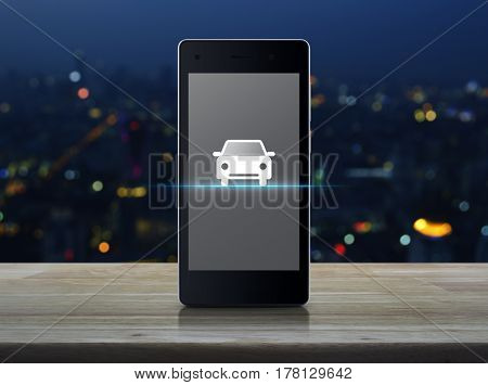 Car flat icon on modern smart phone screen on wooden table over blur colorful night light of city tower Internet business service transportation concept