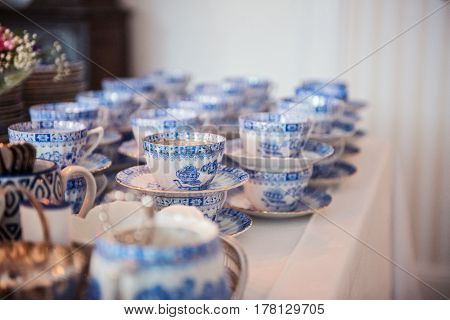 Vintage collection of blue porcelain tea set with teapot and teacups. Classic old blue porcelain tea set in tea shop.