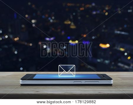 email icon on modern smart phone screen on wooden table over blur colorful night light city tower Business communication concept