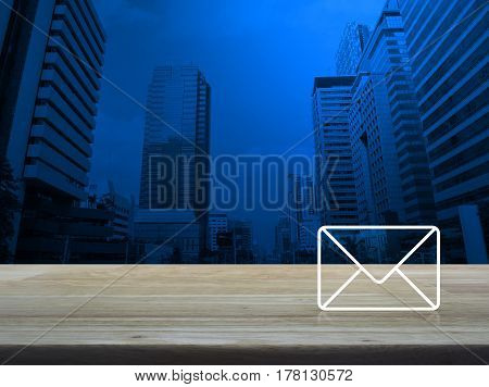 Mail icon on wooden table over modern office city tower background Contact us concept