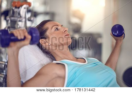 Attractive middle-aged woman working out in a gym training with a pair of dumbbells in a close up view in a health and fitness concept