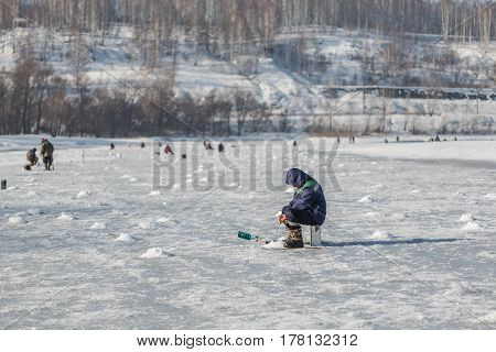Fishermen on winter fishing on ice of the frozen river