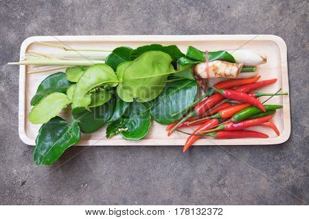 Thai Tom Yam soup herbs and spices lemongrass kaffir lime leaves galangal and chilli in tray wood