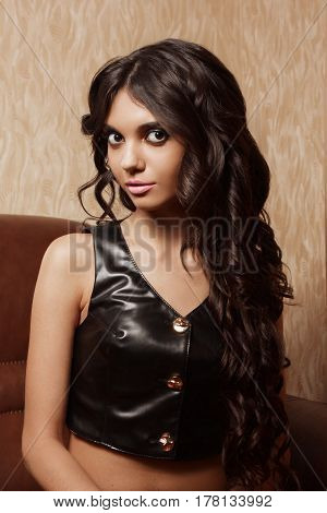 Young girl with long black hair in a leather vest. A very attractive woman with big eyes. Face close-up.