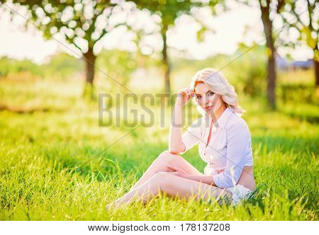 Smiling beautiful young girl sitting on grass in the garden