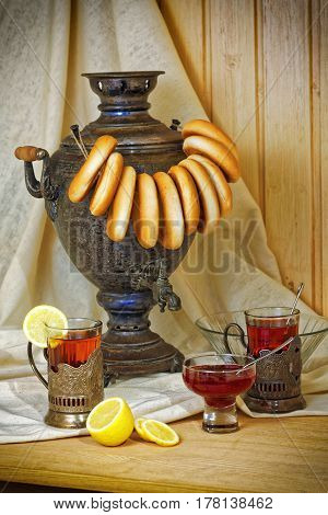 Russian samovar, tea with lemon in faceted glasses with cup holders and bublik. Tinted photo in vintage style.