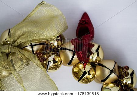 A golden bow wreath with a sparkly red shoe bauble