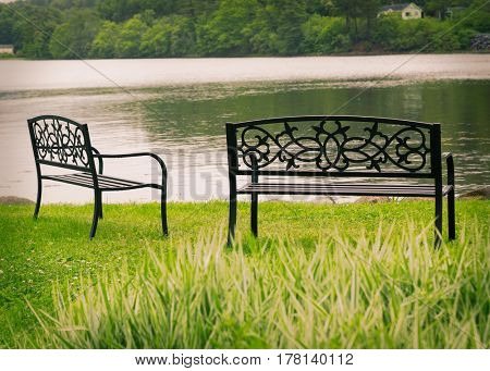 Decorative metal park benches overlooking still water.