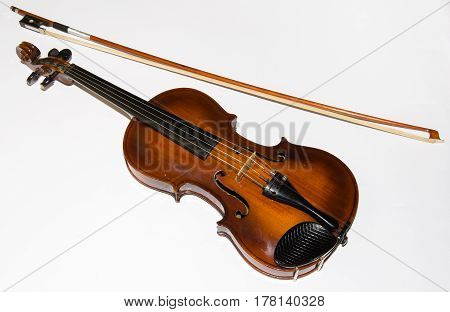 Old wooden violin with bow isolated on a white background