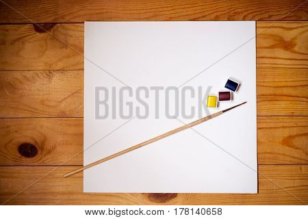 Watercolor paints brush for painting and paper sheet on wooden background. Top view.
