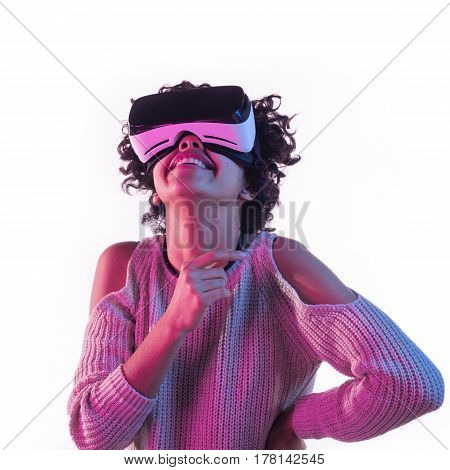 Cheerful young woman having the VR experience on the white background.