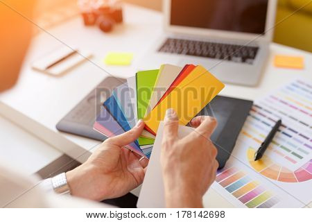 Back view of a designer choosing the colors from a template card at the workplace.