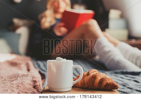 The cocoa with marshmallow and a cornetto on the bed with reading a book young woman.