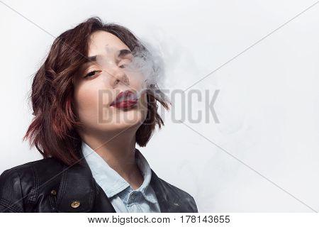 Cool woman looking at camera and puffing a smoke. Horizontal studio shot.