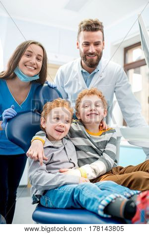 Portrait of happy young boys sitting on the chair with dentist and woman assistant at the dental office