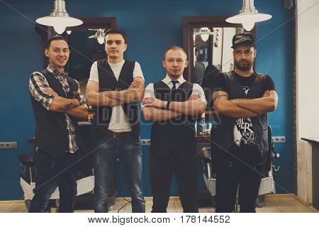 Team of barbers in modern barbershop. Four masculine male hairstylists standing indoors at workplace in hair salon