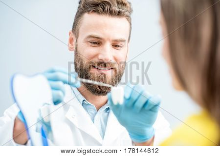 Handsome dentist consulting woman patient holding tooth model at the dental office