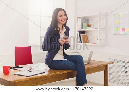 Happy at work. Cheerful businesswoman with mobile. Female worker checking schedule on her phone at workplace