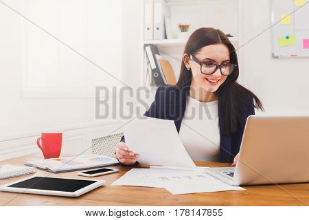 Succesfull woman, female carreer concept. Beautiful young businesswoman sitting by wooden desk with laptop. Modern office worker in white room interior.