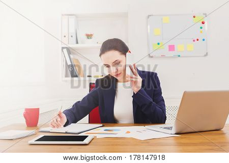 Making call in office. Businesswoman with mobile at workplace, busy working day