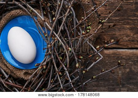 One big egg on a blue plate in a nest with spring branches on an old wooden table