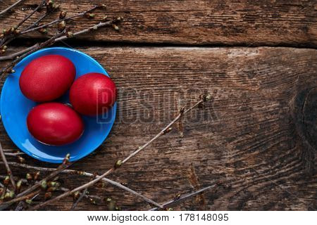 Three Easter red eggs on a blue plate in the nest with spring branches on an old wooden table
