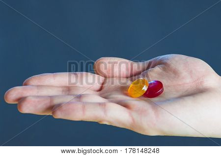 Two Pills Red And Yellow On The Palm In The Hand Medicine