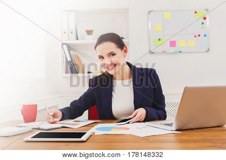 Succesfull businesswoman, female carreer concept. Young woman with laptop, happy at work. Modern office worker in white room interior.
