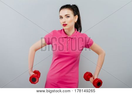 Young beautiful woman playing with two dumbbells on grey background.