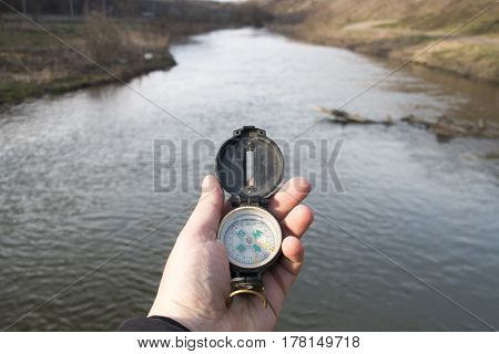 Man traveler holding a compass. On the background - beautiful river.