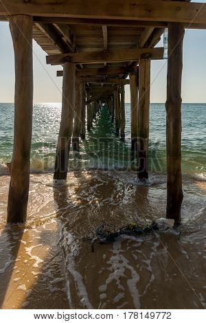 View from underneath a wooden pier on a tropical island.