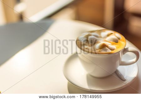 A latte coffee with decorative froth in white cup at golden hour with selective focus.