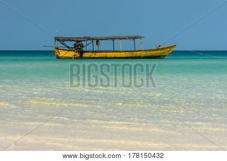 Old Long Tail Boat Anchored Just Off Of Shore.
