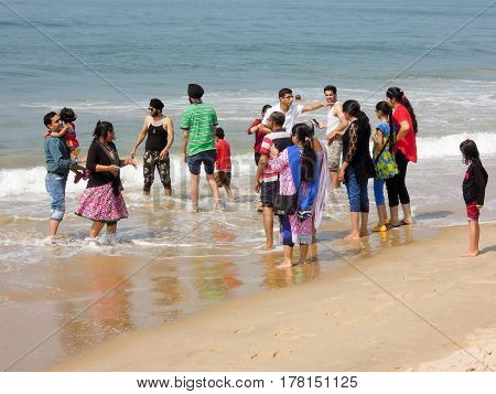 Indian Tourists Dangling Them Feet On The Beach Of Candolim