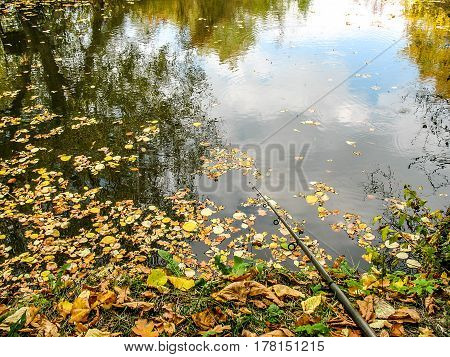 Fishing rod on the river bank, autumn leaves on the water on the autumn fishing