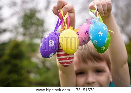 Different Color Easter Eggs In A Child's Hands- Egg Hunt
