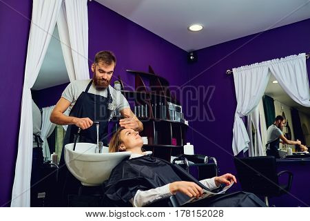 A hairdresser  man washes hair head to the client in the chair barber shop.