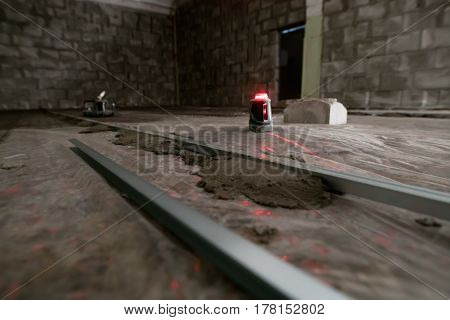 Electronic floor flatness meter with red light in studio being repaired