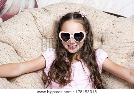 portrait of a little girl in pink sunglasses on the armchair