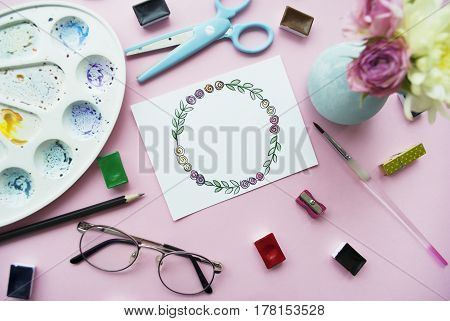 Artist's workspace. Floral wreath frame painted with watercolor vase with a bouquet of flowers glasses paintbrush scissors watercolor. Flat lay.